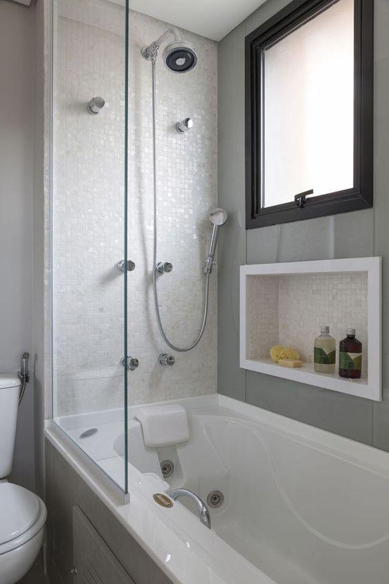 banheiro com banheira e meia parede de vidro