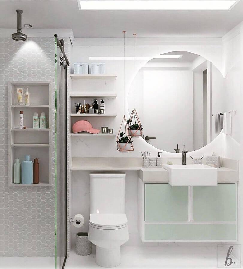 Decoração clean com armário claro e espelho redondo.
