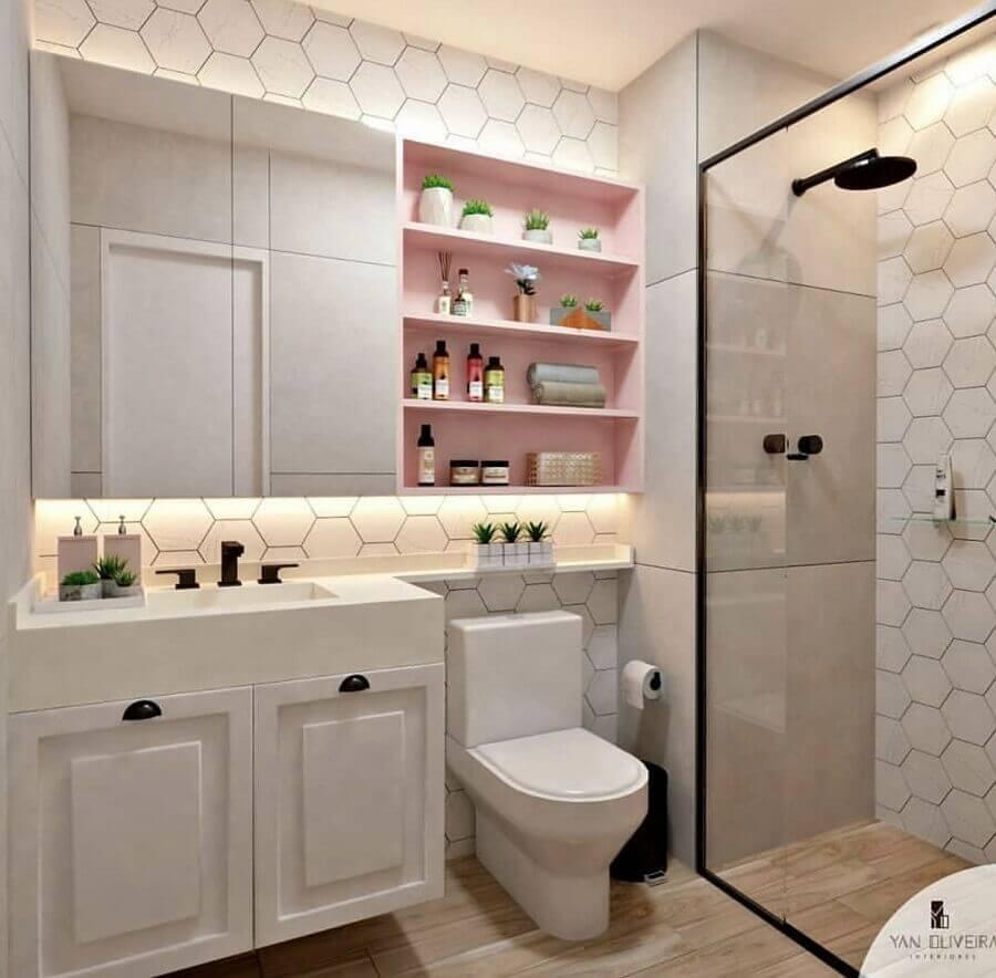 Decoração clean com armário branco, prateleira rosa e revestimento geométrico.