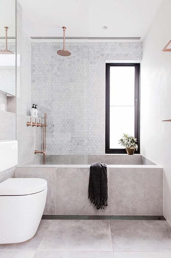 Decoração simples com banheira e revestimento cinza.