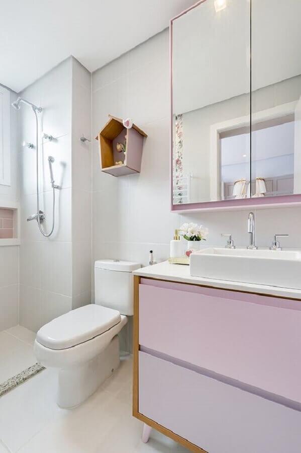 Decoração simples com armário rosa e acabamento de madeira.