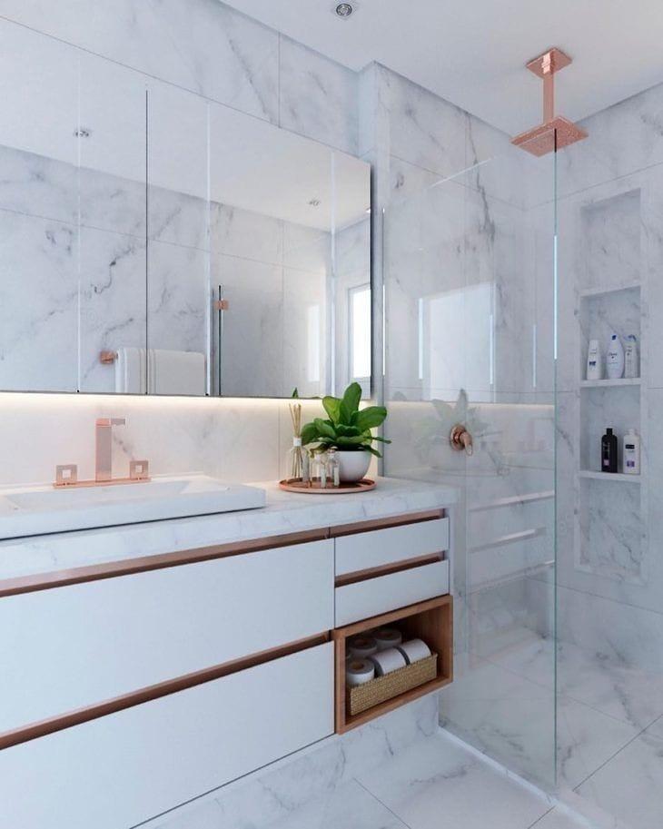 Decoração luxuosa com armário branco e revestimento de mármore.
