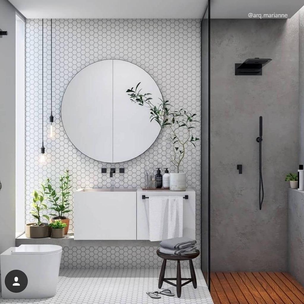 Decoração moderna com parede de cimento queimado, espelho redondo e piso de madeira.