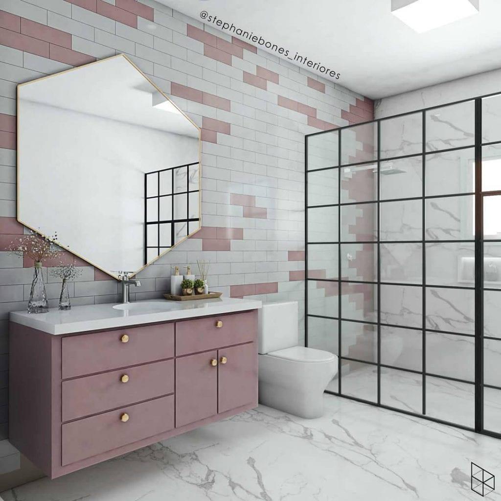 Banheiro feminino moderno com armário rosa e azulejo de tijolinho.