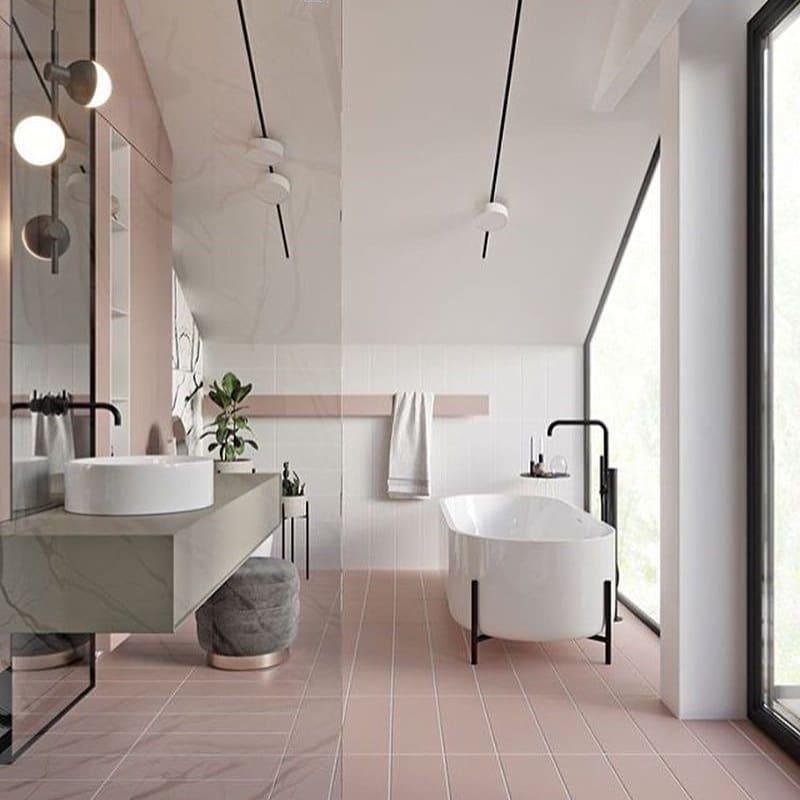Banheiro feminino luxuoso com piso rosa.