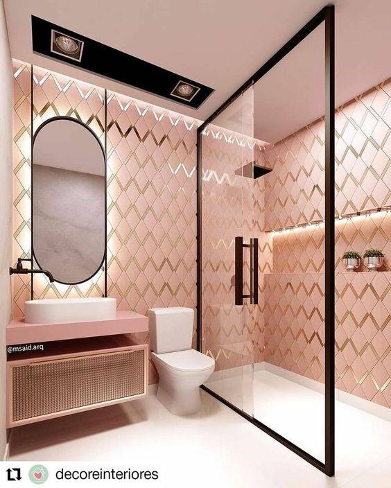 Banheiro feminino moderno com azulejo geométrico rosa e dourado.