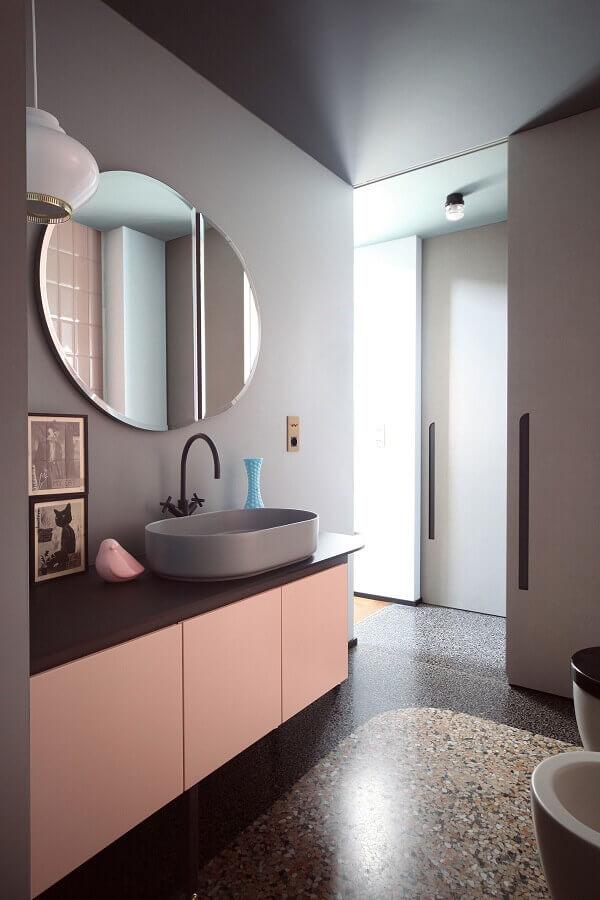 Banheiro feminino moderna com armário rosa e quadros.
