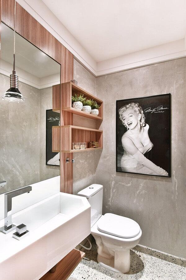 Banheiro feminino simples com quadro.