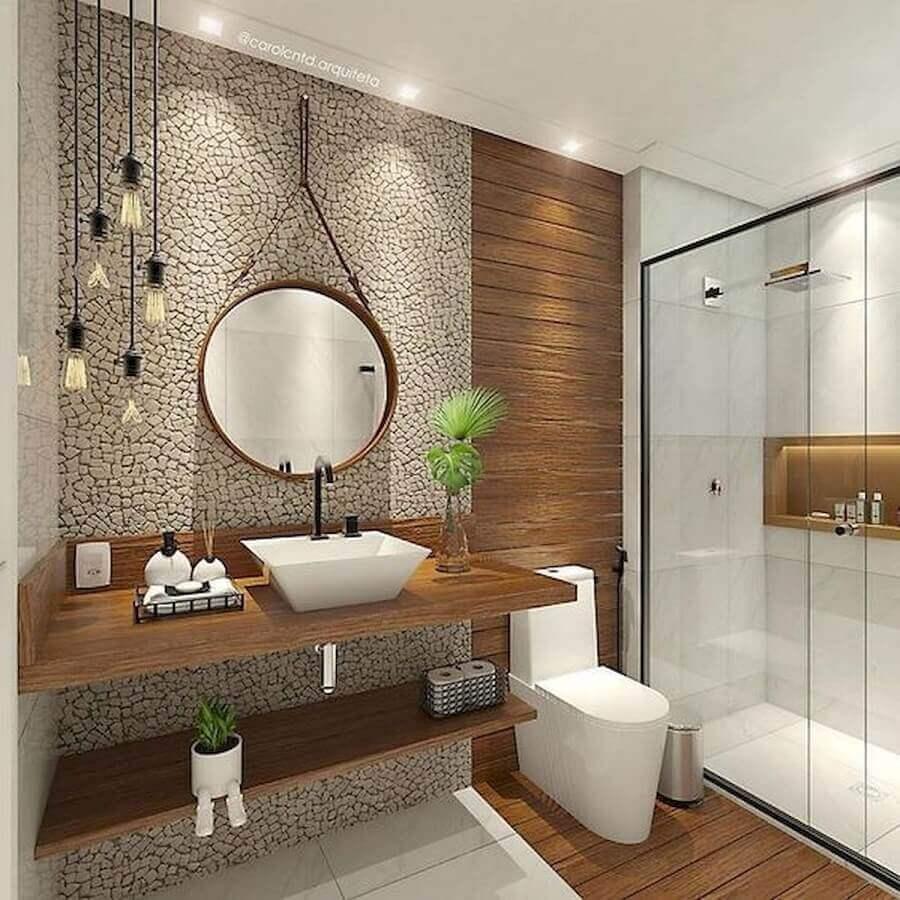 Banheiro feminino moderno com bancada de madeira e acabamento de pedra.