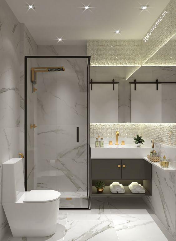 Banheiro feminino luxuoso com acabamento de mármore branco e decoração dourada.