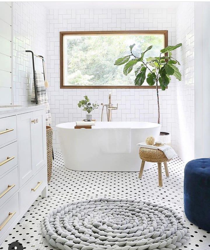 Decoração clean com banheira moderna, azulejo de tijolinho branco e piso com cerâmica branca e preto.