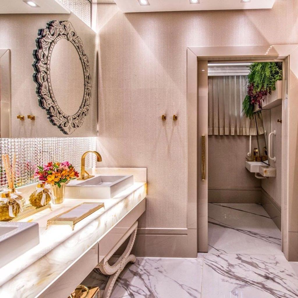 Banheiro feminino com bancada de mármore, decoração dourada e espelho bisotado.