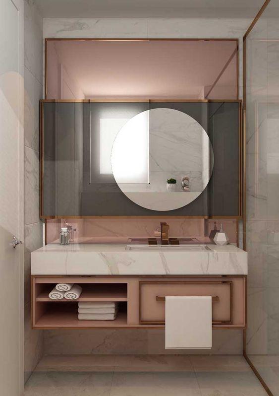 Banheiro feminino luxuosa com armário rosa, bancada de silestone e espelho redondo.
