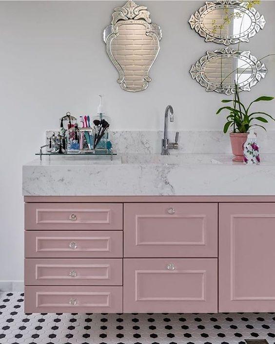 Banheiro feminino com armário rosa e espelho bisotado.