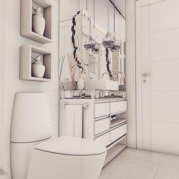 Banheiro feminino luxuoso com decoração clean e espelho bisotado.