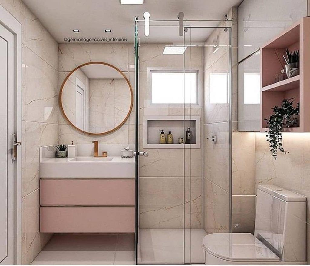 Banheiro feminino pequeno com espelho redondo e armário rosa.