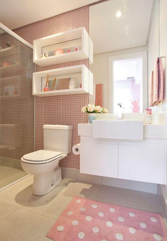 Banheiro feminino pequeno com espelho quadrado e pastilhas de vidro.