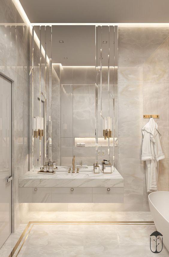 Banheiro feminino luxuoso com espelho bisotado e acabamento de porcelanato.