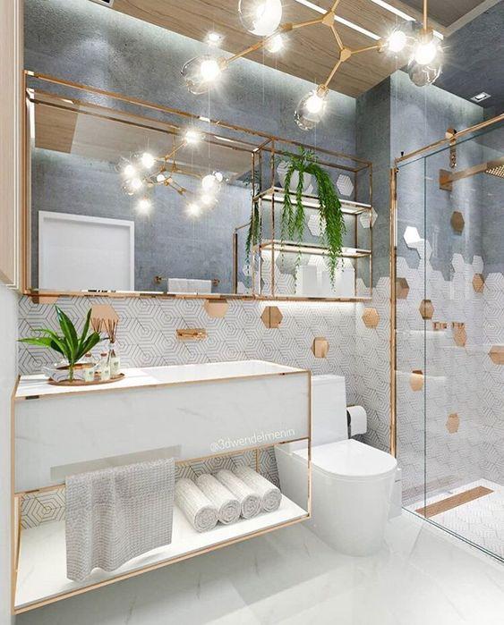 Banheiro feminino branco e dourado com bancada de porcelanato.