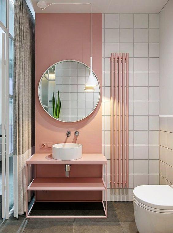 Banheiro feminino moderno com bancada rosa de metal.