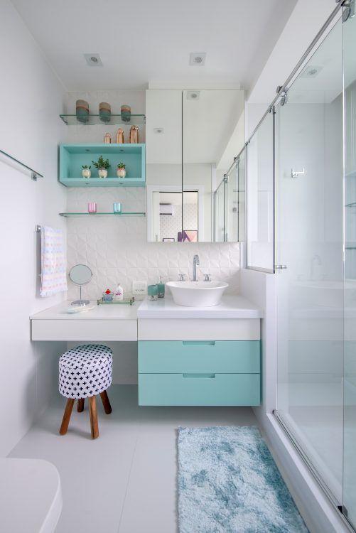 Banheiro feminino simples com armário azul, penteadeira, nichos azuis e prateleira de vidro.