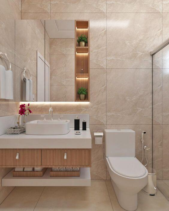 Banheiro feminino pequeno com armário de madeira, bancada branca e espelho iluminado.