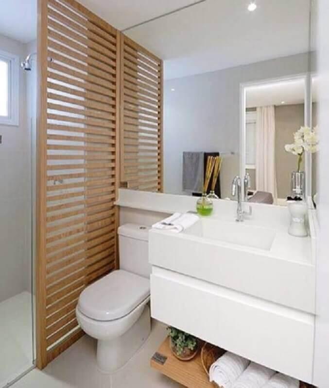 Decoração simples com armário branco e detalhe de madeira no box.