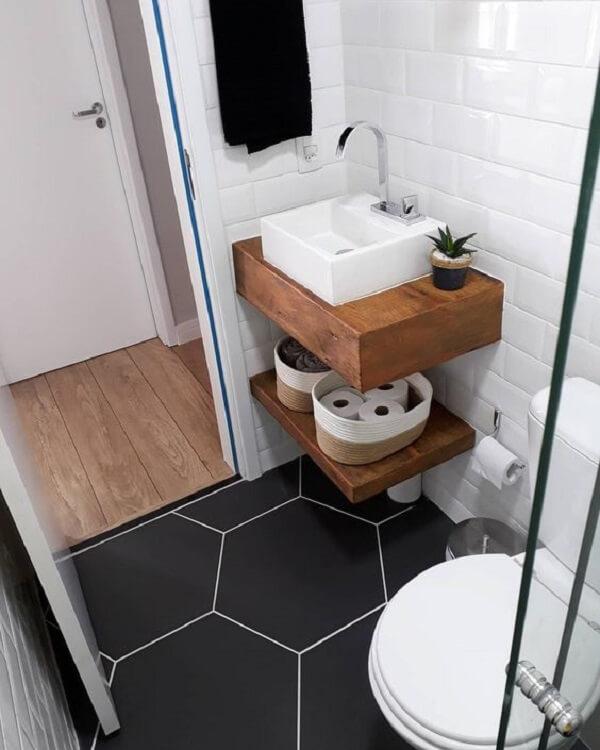 Decoração moderna com bancada rústica de madeira e piso geométrico preto.