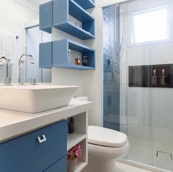 Decoração com armário azul, nichos e azulejo colorido no box.