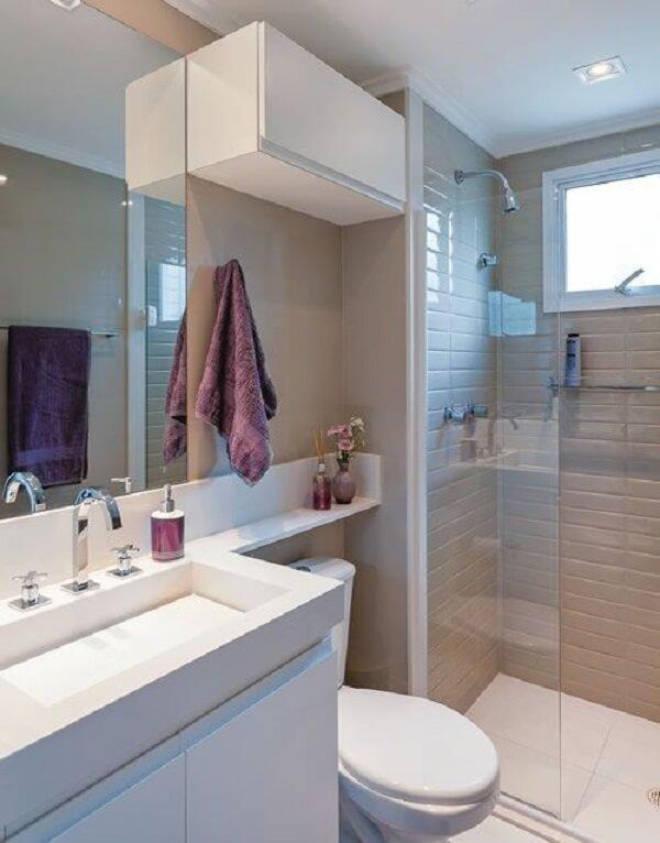 Decoração simples com pia branca, armários brancos e azulejo neutro.