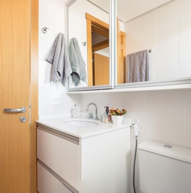 Decoração simples com armário branco e espelho com armário.