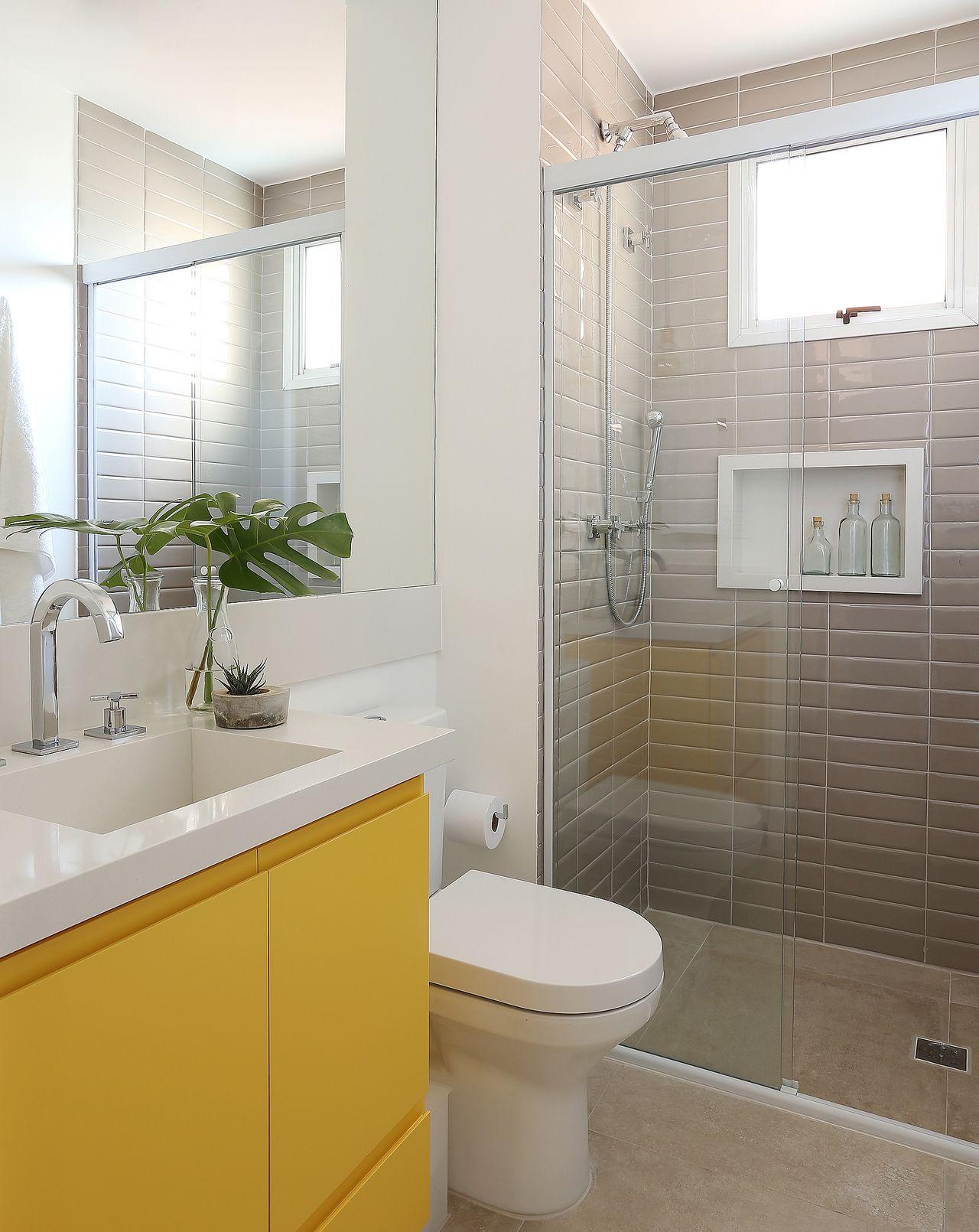Banheiro pequeno com armário amarelo.