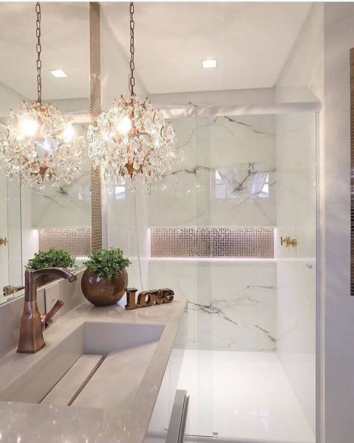 Banheiro pequeno com lustre e revestimento de mármore.