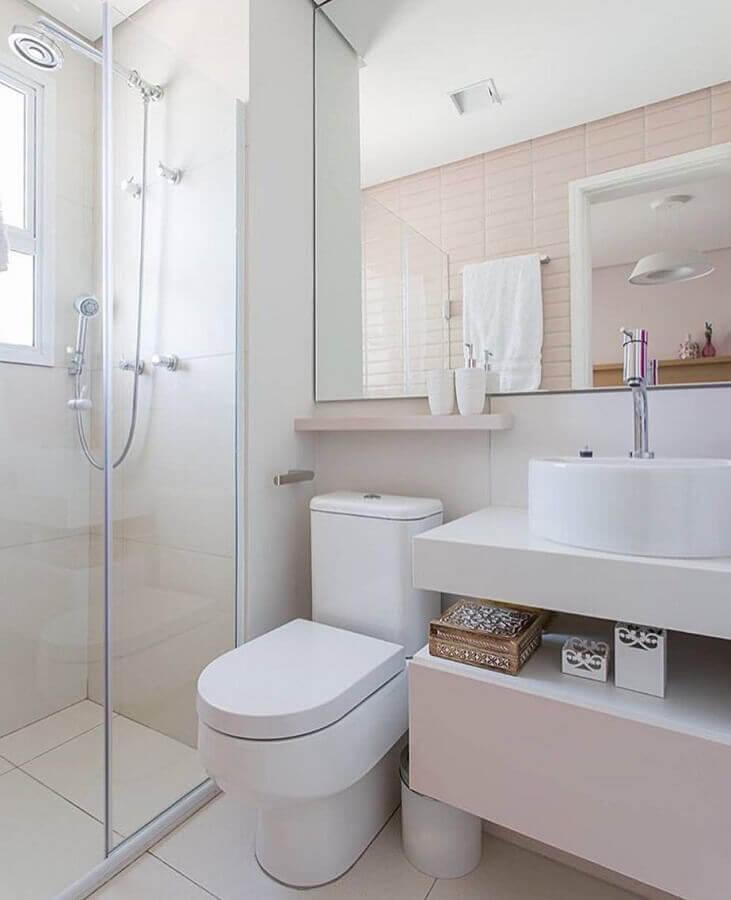 Decoração simples com armário branco, cuba redonda e azulejo de tijolinho rosa.