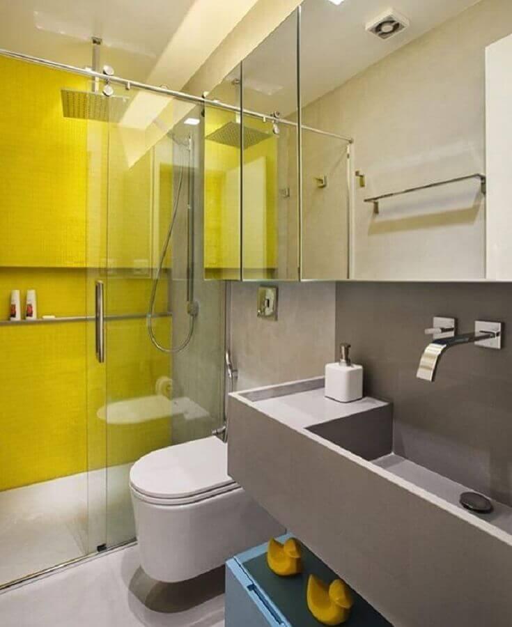 Banheiro pequeno moderno com azulejo amarelo e pia esculpida cinza.