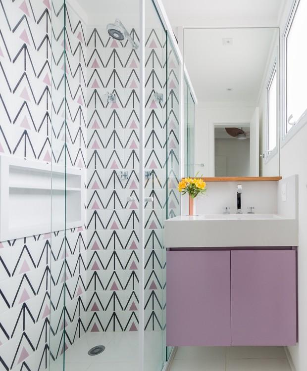 Banheiro pequeno com azulejo decorado e armário rosa.