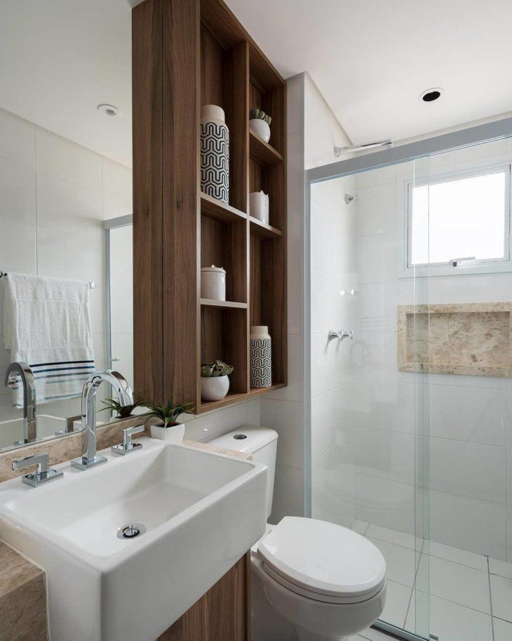Banheiro pequeno simples com nichos de madeira.