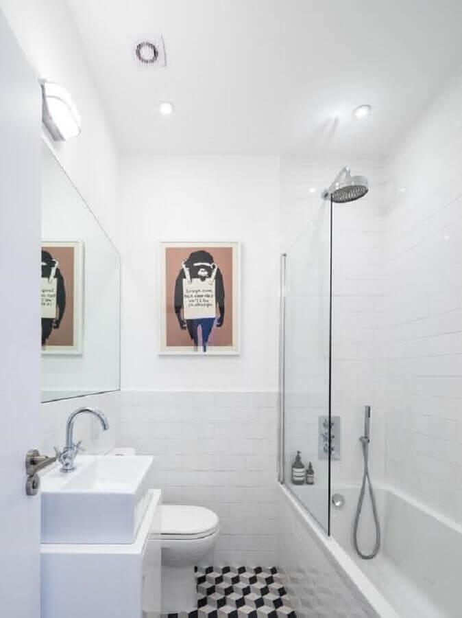 Decoração simples com banheira e quadro decorado.