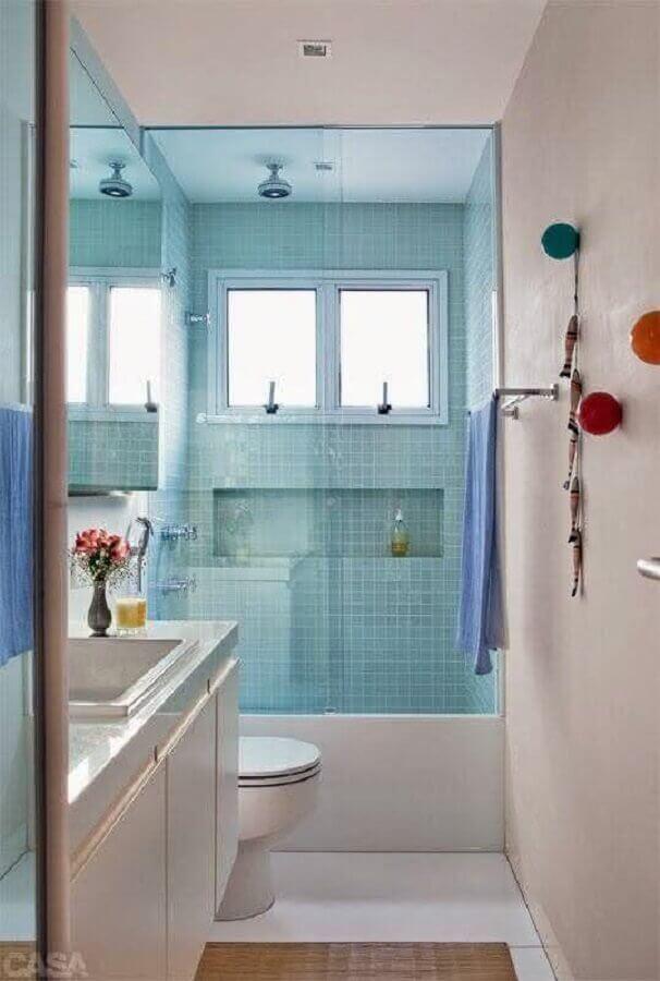 Banheiro pequeno com armário branco e pastilha azul no box.