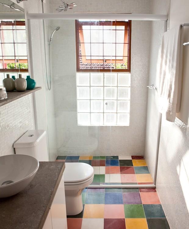 Banheiro pequeno com pastilha branca e piso colorido.