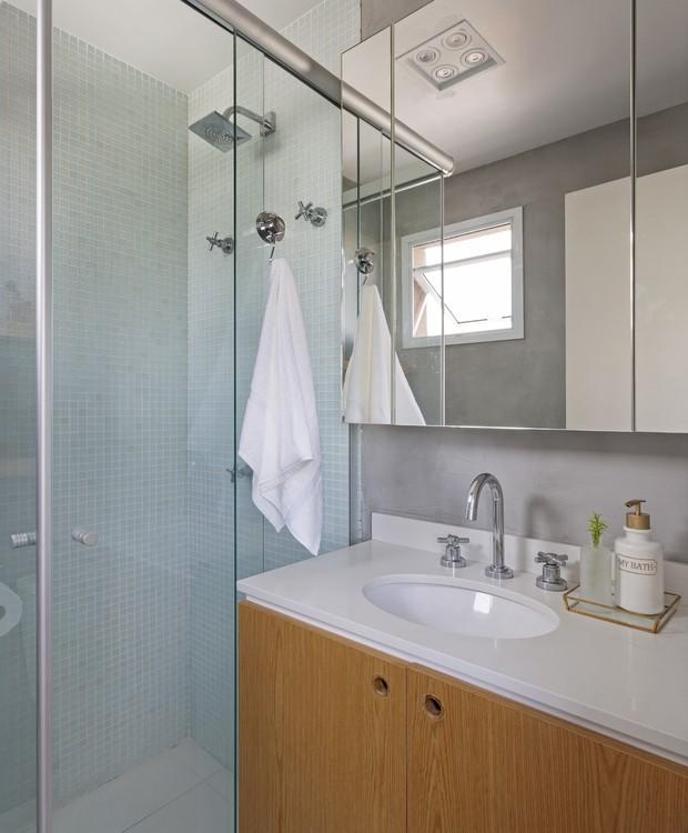 Banheiro pequeno com armário de madeira e parede de cimento queimado.