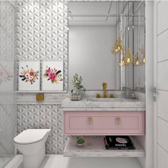 Banheiro pequeno feminino com armário rosa, quadro decorado e pendente suspenso dourado.