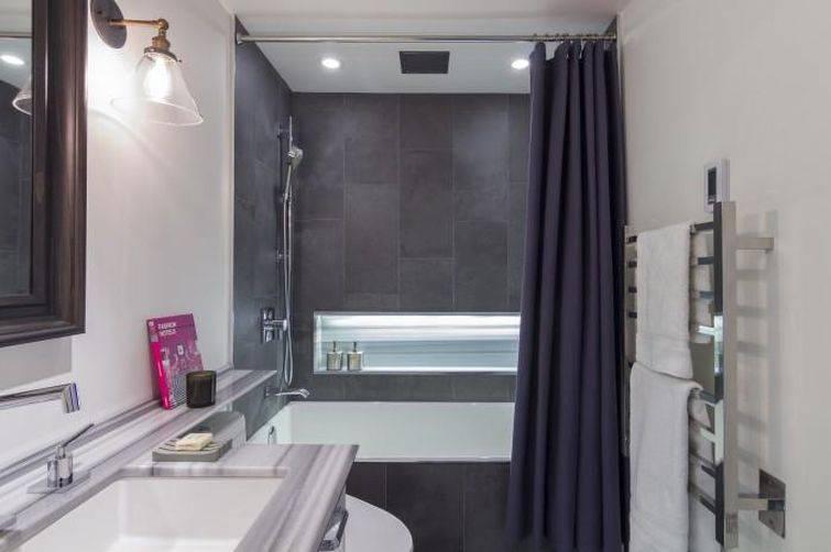 Banheiro pequeno cinza com banheira.