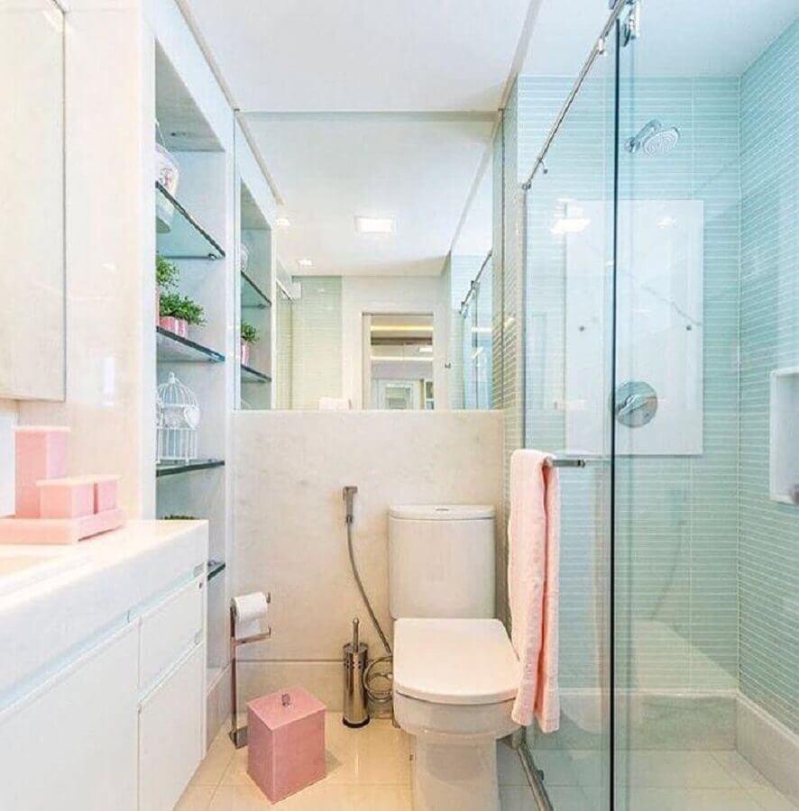 Banheiro pequeno com prateleiras de vidro e azulejo azul.