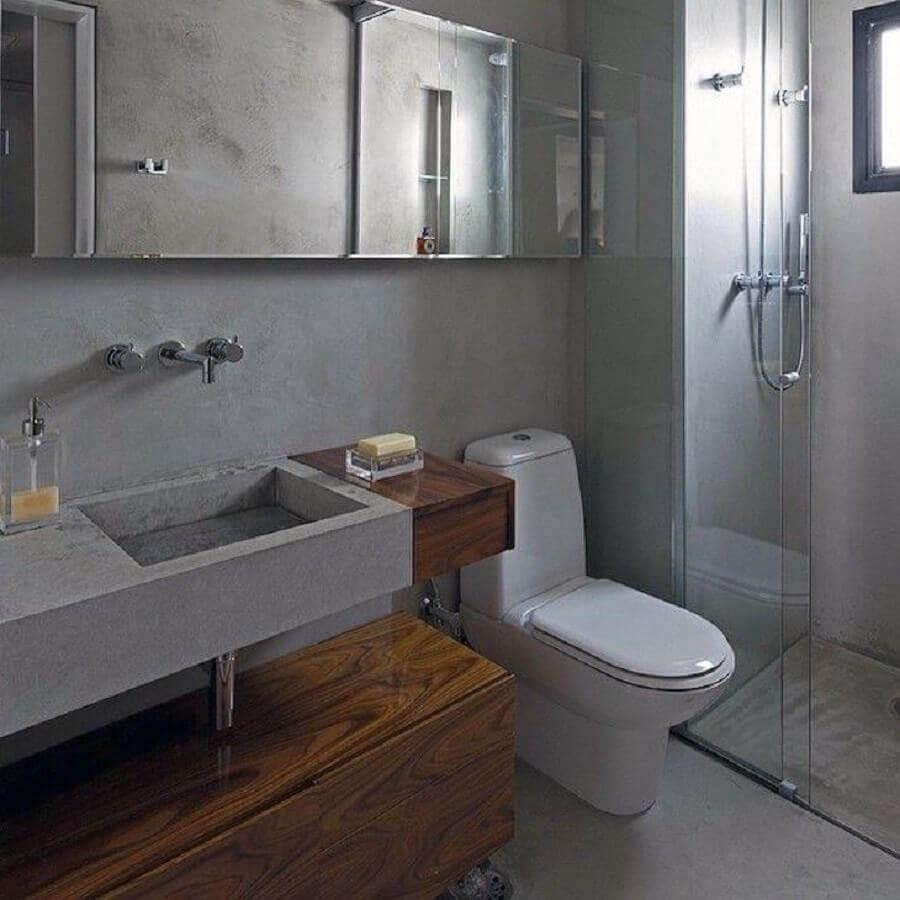 Banheiro pequeno cinza com armário de madeira.