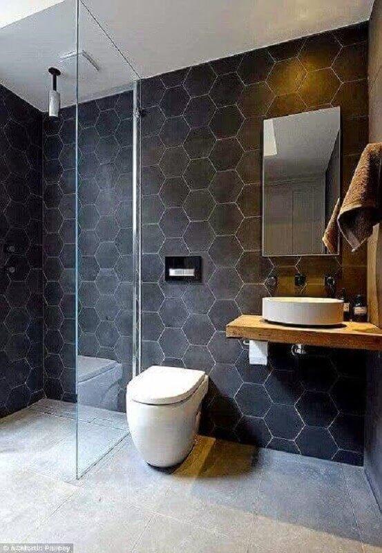 Banheiro pequeno com azulejo geométrico preto.