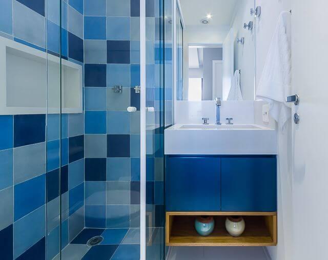 Banheiro pequeno com armário azul e azulejo azul.