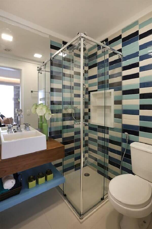 Banheiro pequeno com bancada de madeira e azulejo de tijolinho colorido.