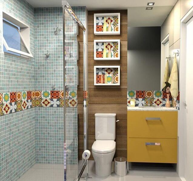 Banheiro pequeno moderno com armário amarelo e azulejo colorido.