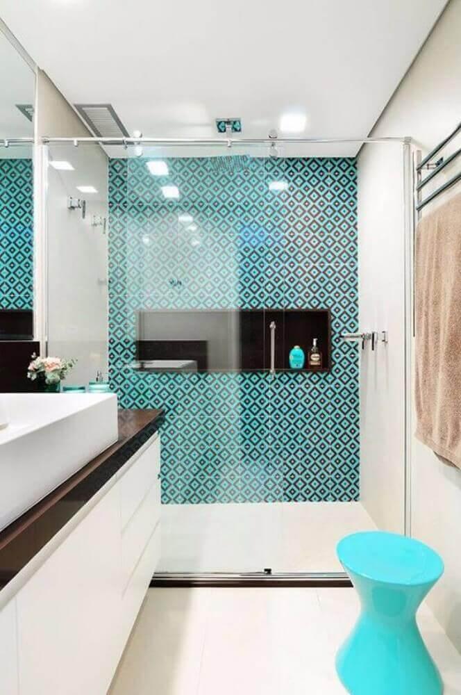 Banheiro pequeno com nicho de madeira e azulejo decorado azul.